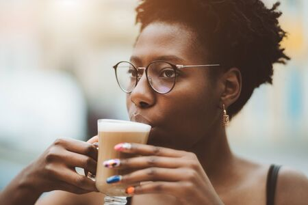 A close-up portrait of a young charming African female in spectacles outdoors holding a glass of delicious coffee latte; cute black girl in glasses and with nail art is drinking cocoa in a street cafe