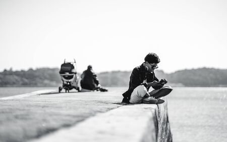 Black and white shot with a selective focus on a young African female in a denim jacket and sunglasses sitting on a concrete pier and using her smartphone; a silhouette of a man with a pram abaft her Stockfoto