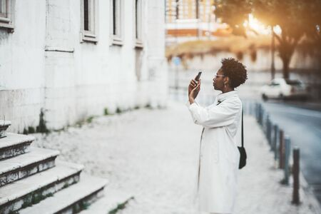 A modish young African tourist female with nail-art and curly afro hair and in spectacles and a white cloak is photographing attractions outdoors during her trip using a camera of her smartphone
