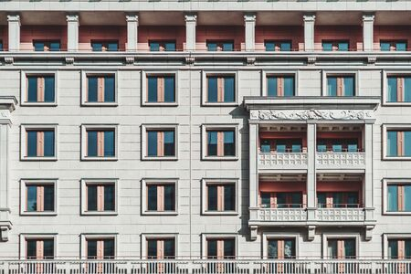 A grayish facade of a modern multi-storey building made in a typical modern Russian architecture style in Moscow: plenty of windows, balconies, bas-relief; a regular house frontage texture Foto de archivo