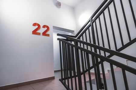 A typical flight of stairs in an office business skyscraper: clean white walls, metal fencing of the stairway, bright light, door to the floor, big orange digits