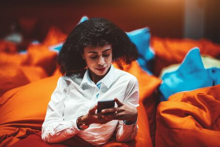 Beautiful African-American businesswoman is relaxing on an orange cushion in a lounge area of her office and using a smartphone; a biracial woman entrepreneur with a cellphone in a chillout zone