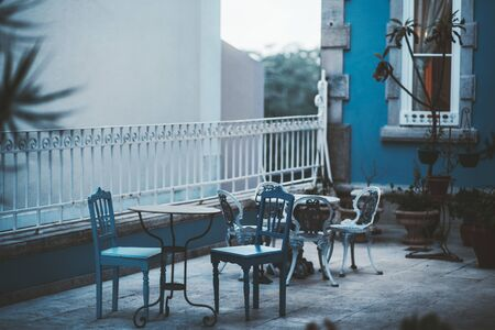 An evening shot with a shallow depth of field of a small patio in Sintra, Portugal, with two antique dining tables outdoors with a selective focus on two old elegant carved chairs in the front