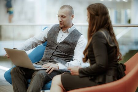 A handsome cheerful businessman is showing to his female colleague something on a screen of his laptop while both sitting on armchairs in an open space area of a contemporary office during a meeting Фото со стока