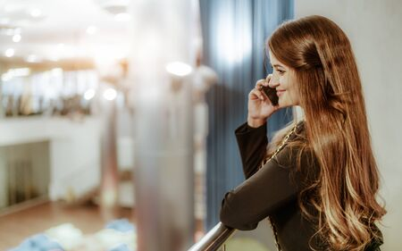 A cheerful caucasian businesswoman is phoning while leaning the railing of a balcony of an office open-space area; a charming mature smiling woman entrepreneur having phone conversation indoors Фото со стока