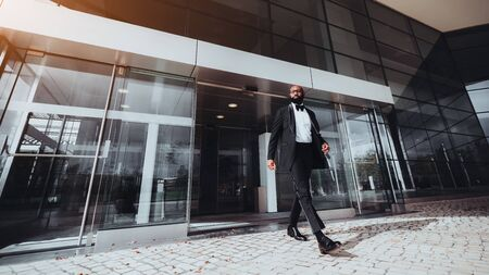 An elegant bearded bald African man entrepreneur is leaving a business skyscraper, he has just passed automatic sliding doors; a black businessman in a formal suit is leaving a modern building Zdjęcie Seryjne