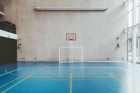 Vorderansicht des Platzes in der Turnhalle; ein modernes Indoor-Bürostadion mit Basketballkorb und -korb, Fußballtor, blauem Boden, einer Betonwand mit einer nicht eingesetzten Projektionswand darüber Standard-Bild