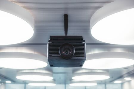 A black modern projector with a plastic case and a huge lens with aberrations in it mounted to a striped ceiling with multiple huge circle ceiling lamps lighting a modern conference hall