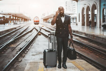 An adult bald bearded fancy African man entrepreneur with travel bags is adjusting his spectacles while standing on a railway platform with track junctions behind; copy space area on the left Stok Fotoğraf