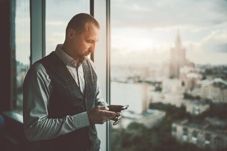 A confident serious handsome caucasian man entrepreneur using his smartphone near a panoramic window of an office skyscraper with cityscape and a high-rise outside; a copy space area on the right