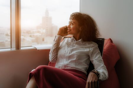 A cheerful charming young African-American woman entrepreneur is sitting on an armchair in an office area next to the window and having a phone conversation, a cityscape with a high-rise outside