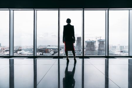 Rearview of a female entrepreneur on the top of a modern business office skyscraper standing near big panoramic windows and pensively looking at cityscape and construction site; floor with reflections