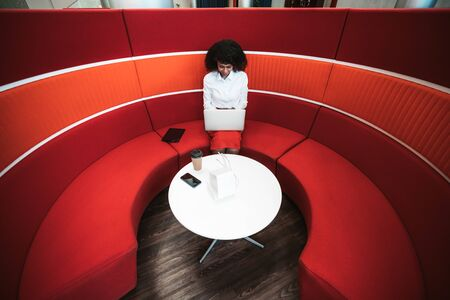 A cheerful African-American woman entrepreneur is sitting in a cozy office lounge area on a curved red sofa and using a laptop; paper cup, dock station and a cellphone on the table, tablet pc near her Фото со стока