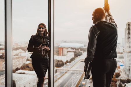 Two mature business partners near a panoramic window indoors of an office skyscraper: a man with a laptop and his caucasian female colleague with a smartphone; the cityscape and the highway outside
