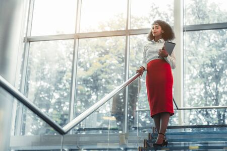 Dazzling African-American businesswoman with a tablet pc is standing on the top of a glass office staircase with chrome railing, a copy space area on the left for an ad text message or your logo