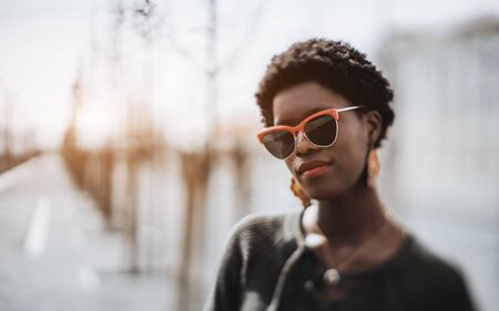 True tilt-shift portrait with selective focus on half of the face and part of the hair of a charming African girl in sunglasses standing outdoors, a copy space place on the left for an ad text or logo