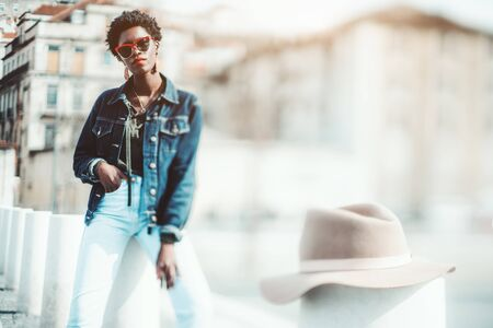 True tilt-shift shot with selective focus on an elegant African female in denim closes, sunglasses and earrings leaning against a stone bollard outdoors and on a velour hat on a pole in the foreground Stok Fotoğraf
