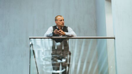 An elegant pensive caucasian businessman is thoughtfully looking aside while leaning on a chrome railing of a glazed balcony indoors of an office open-space area and holding a cellphone in his hands 版權商用圖片
