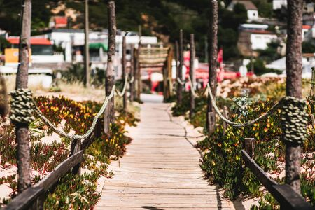 A long wooden outdoor passageway in a warm summer resort from the beach to the inner area: wooden fence, rope tied between pillars, shallow depth of field with a selective focus on the foreground Reklamní fotografie