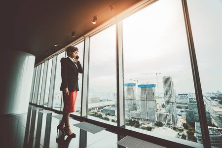 A confident successful African-American woman entrepreneur is talking on the phone while standing in front of a panoramic window of a luxurious office skyscraper with a construction site outside Stock Photo