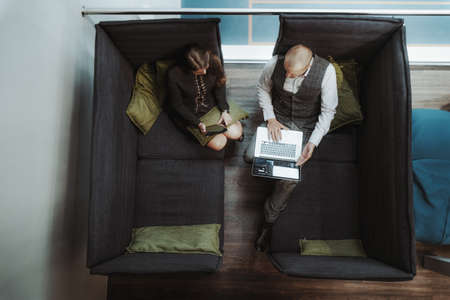 View from above of two successful business people in a cozy co-working area of a modern office having a business meeting: a man entrepreneur with a laptop, his female colleague with a digital tablet