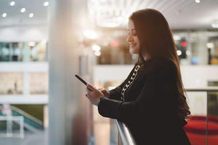 A smiling caucasian businesswoman using a smartphone while leaning on the railing of a balcony of an office open-space area; a charming plus size woman entrepreneur sending a message with a cellphone