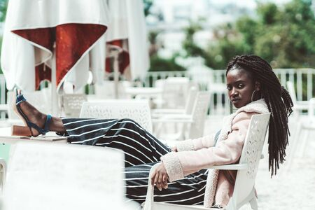 An arrogant young charming African female with braided hair and big earrings is sitting on a white plastic armchair outdoors in an empty street cafe with her feet on the table, a cold sunny day Zdjęcie Seryjne