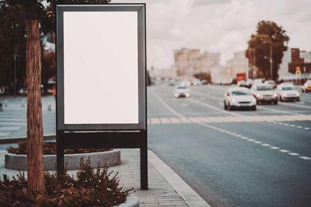 Mockup of a blank information poster in urban settings near a road with a crosswalk; an empty vertical street banner template on the sidewalk; an outdoor billboard placeholder mock-up near the highway