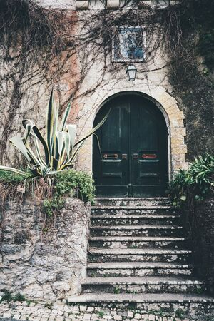 An antique wooden gate in the recess of a stone arch in the wall with a flaked plaster, stony stairs in front, a small lantern on the top surrounded with dry branches, Sintra, Portugal