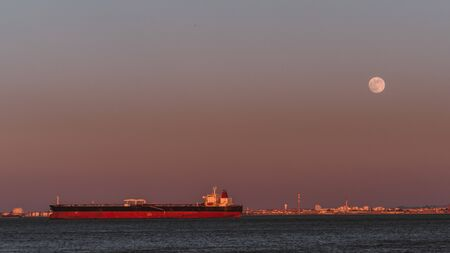 Huge long red and black tanker on the Tagus river on the sunset with the full moon and gentle purple gradient in the background, Lisbon, Portugal Archivio Fotografico