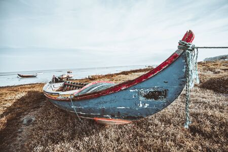 Wide-angle view of an old wooden fishing boat on the riverbank in Alcochete, Portugal: flaked multicolored paint on the wood, grassy ground, multiple other boats and horizon in a defocused background