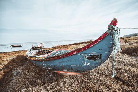 一条老木渔船的广角看法在河岸的在山羊,葡萄牙:在木头,象草地面,多个其他小船和天际的剥落的多彩多姿的油漆在defocused背景中