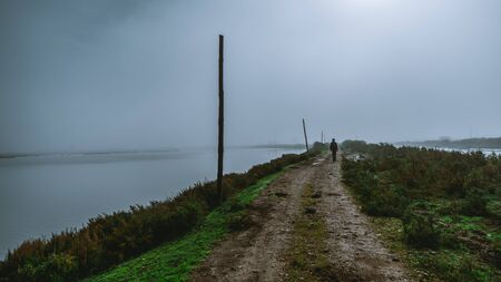 View of a dirt road with a lonely silhouette of a man walking into the distance surrounded by grassy parts and water on both sides and wooden poles on the left side, on a misty dull overcast morning