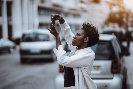 A young charming African woman with a curly afro hair and nail-art, in a white cloak and eyeglasses, is photographing some showplace near an urban road with cars using a rear camera of her smartphone Imagens