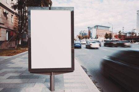 Mock-up of an empty information poster near a highway, long exposure; a blank street banner template on a sidewalk in a city; an outdoor billboard placeholder mockup near the road withblurry cars