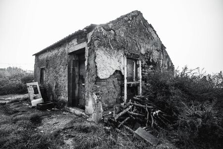 A wide-angle black and white shot of a desolate stone house with rough flaked walls covered with cement, triangle roof. Garbage, bushes, and firewood around. Alcochete, Portugal Stock Photo