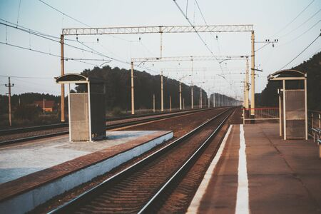 An outdoor train station with several platforms and railroad tracks stretching in a vanishing point in the distance, evening in a Pavino suburban area, Novosibirsk, Russia, shallow depth of field Stok Fotoğraf