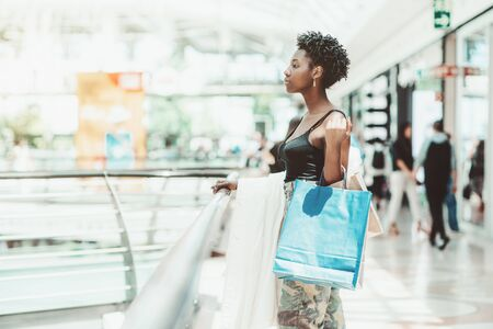 A dazzling young fashionable African female is standing next to the fence in a modern shopping mall with disposable paper bags with purchases in her hand; a copy space place on the left for a message 版權商用圖片