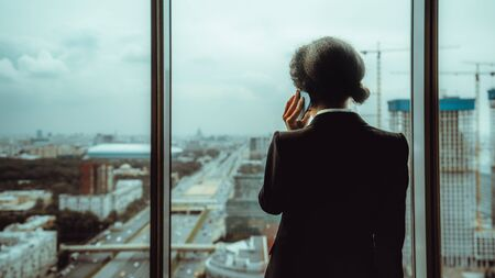 View from behind of a woman entrepreneur speaking on the phone while standing next to a panoramic window of a modern business center and looking outside on the highway, cityscape and construction site