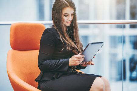 An hispanic businesswoman in a black business casual dress is sitting on an orange armchair indoors of an office open-space area and using her digital tablet PC, with a copy space place on the right
