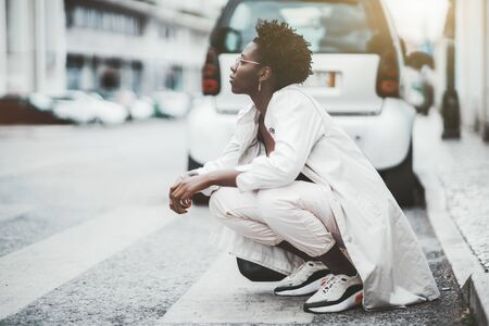 A fancy charming black girl in eyeglasses and a white cloak is squatting at the start of a pedestrian crossing outdoors; young African female in glasses squatted down near the crosswalk and car Stockfoto