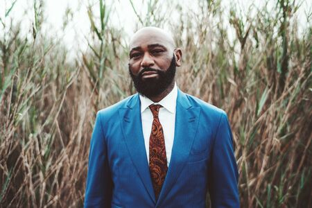 Portrait of a handsome mature bearded bald African man standing in front of thickets of reeds in an elegant blue business costume with a tie; a fancy serious black guy in a formal suit outdoors