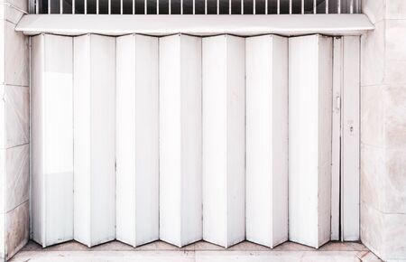A Garage or other entrance closed metal gate texture with white vertical fanfold lines of the door; front view of an accordion-folded painted door of big gates on the street common in Lisbon, Portugal Archivio Fotografico