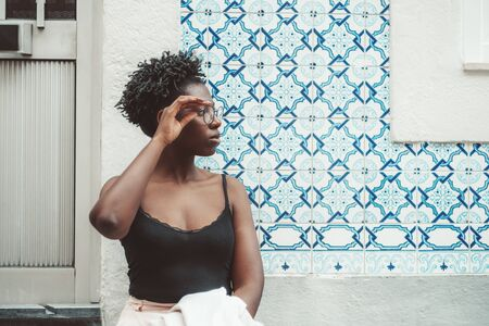Dazzling young African female is adjusting eyeglasses while standing in front of traditional azulejo wall; cute Tanzanian girl in spectacles and a black tank top is fixing her spectacles with hand Archivio Fotografico