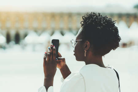 Side view of a dazzling black tourist girl with afro hair, in fancy eyeglasses and a white trench, with a nail-art shooting outdoor sightseeing using a camera of her cellphone on a warm sunny day