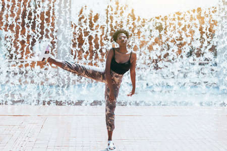 Funny shot with a fancy charming black girl in a sunglasses fooling around, standing on one leg with another leg lifted up doing ballet pas; streams of falling water in background and splashes around