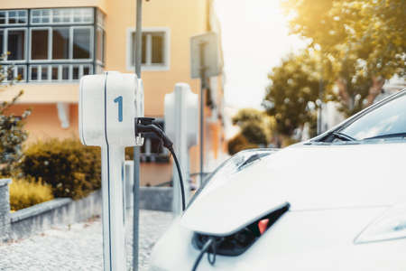 """An electric car charging on a parking lot with a charging station in urban settings; a power supply unit outdoors with an inscription digit """"1"""" with an electric car connected with a power cable"""