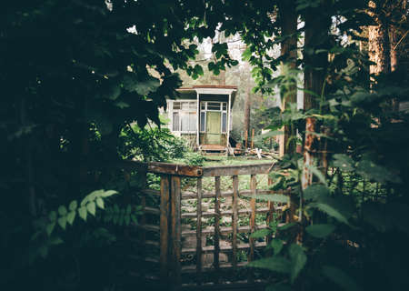 View of a cozy cryptic wooden wicket in a deforused foreground in a tunnel of plants and greenery with a small countryside summer dacha house door visible aloof at the distance in a woods Standard-Bild