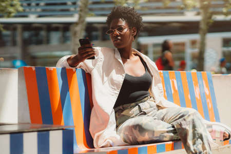 Dazzling young elegant African female in sunglasses is sitting on a motley striped street bench and using a mobile phone to chat with her friend; a charming black girl using a cellphone outdoors