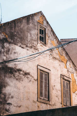 Side vertical shot of an old flaked facade of an antique residential house with a triangle roof and three windows; stretched wires in the foreground, Lisbon, Portugal Stock Photo